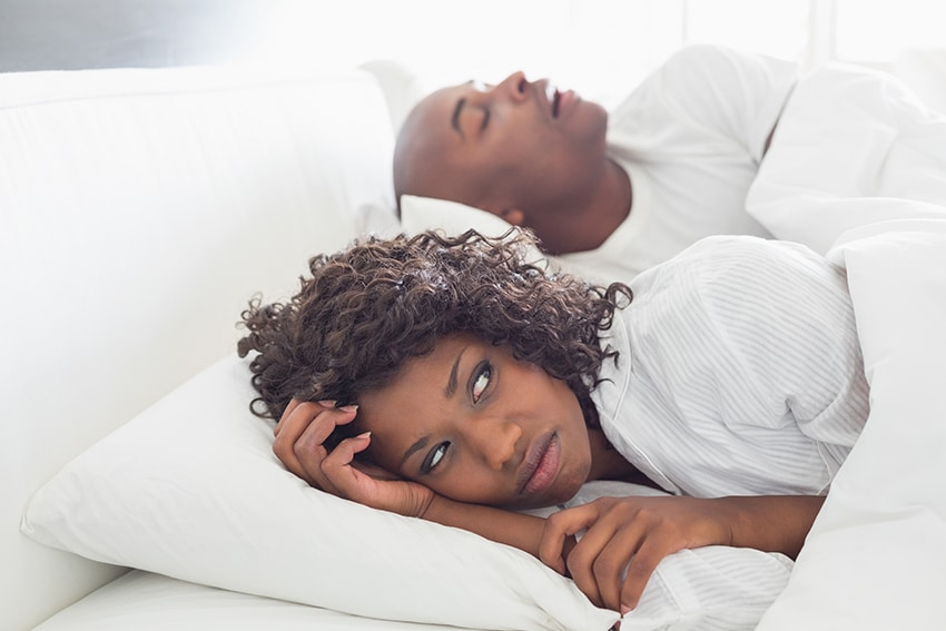 Annoyed wife lays wide awake next to her husband who is snoring loudly in bed