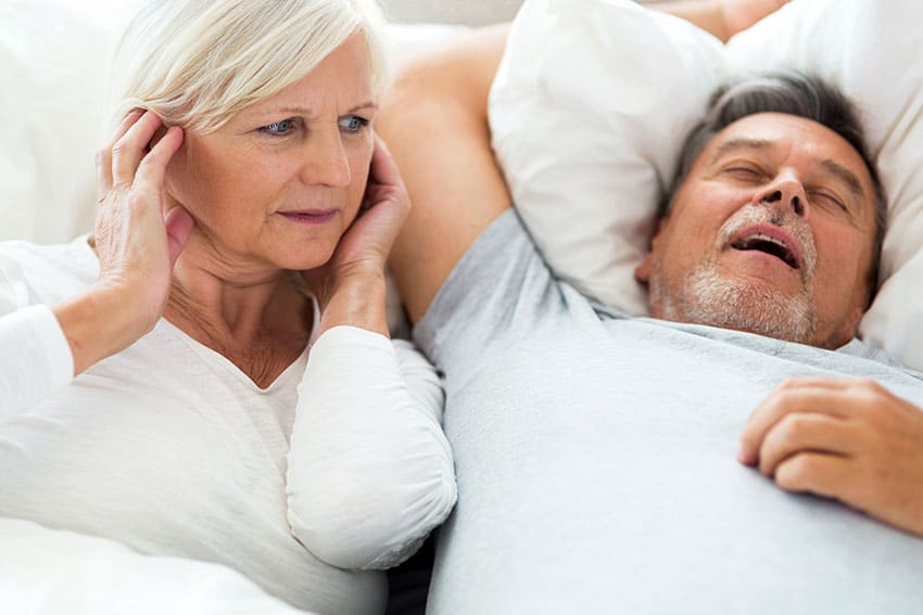 woman covering her ears in bed while husband snores loudly next to her