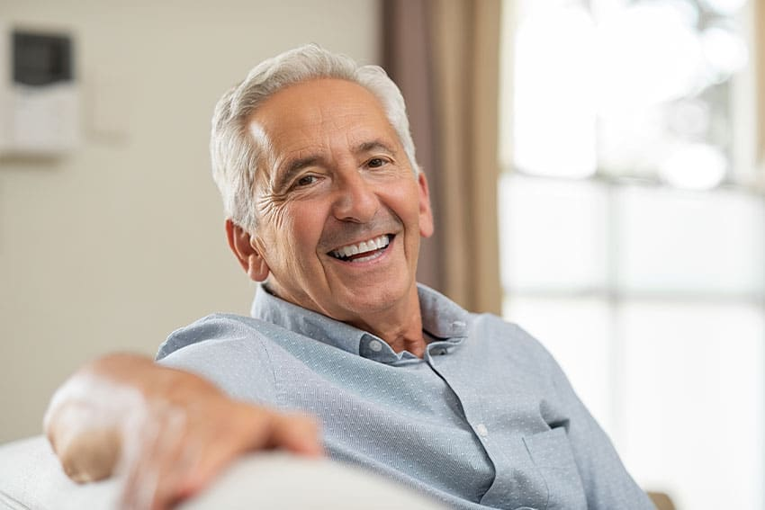 Happy older man laughing at home on the couch