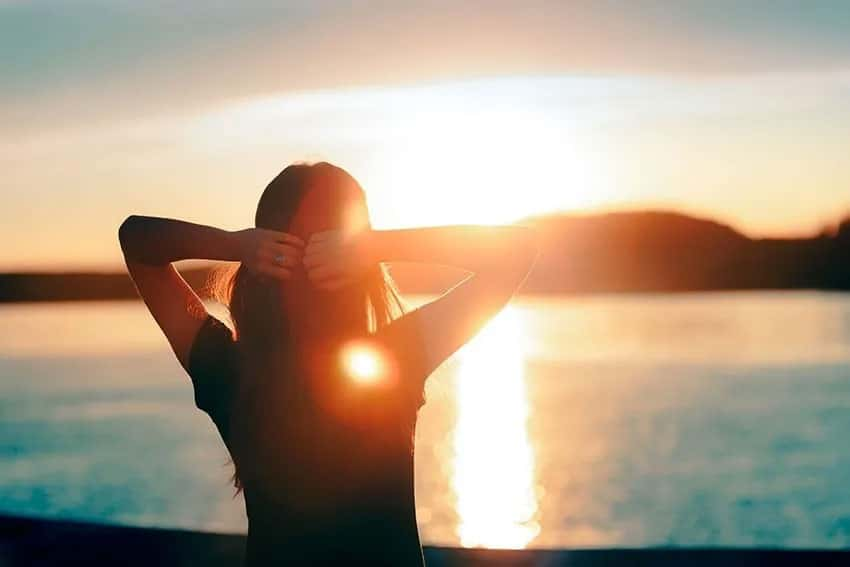 woman looking into the sunshine over a beautiful lake
