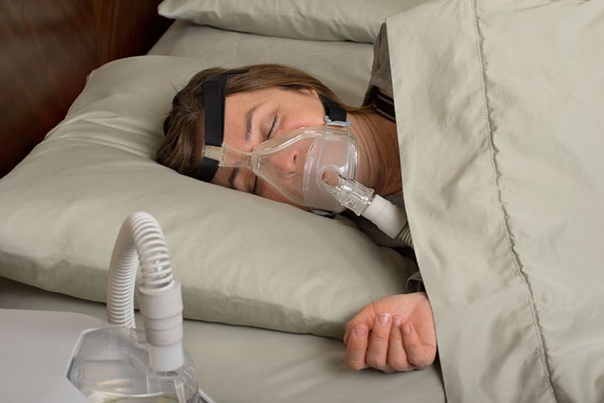 woman laying on her side with a bulky CPAP mask on