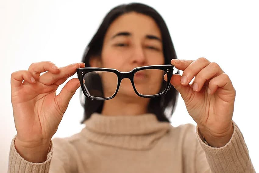 Woman looks through the lenses of her eye glasses, trying to focus