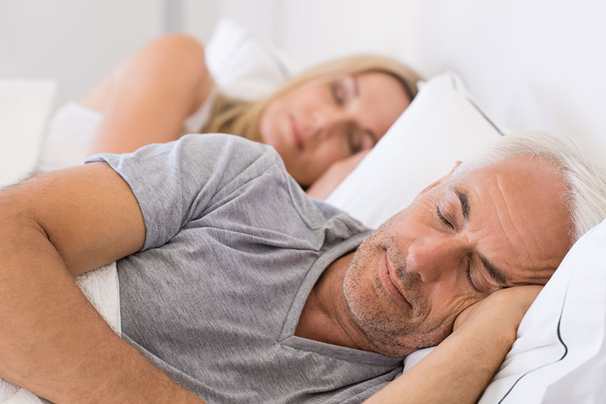 Mature couple laying peacefully in bed together, resting