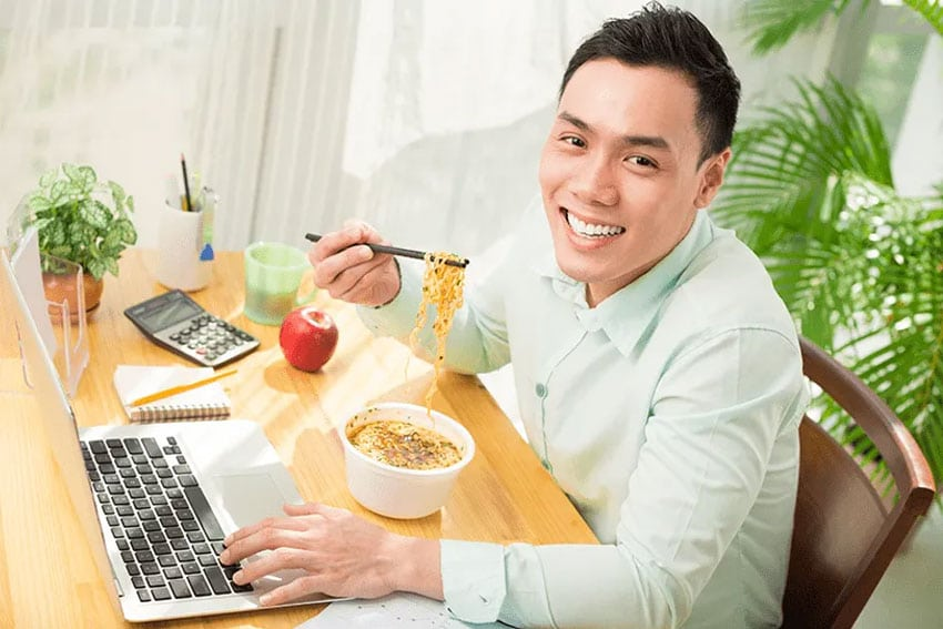 young man eats Asian food while working on this laptop at home