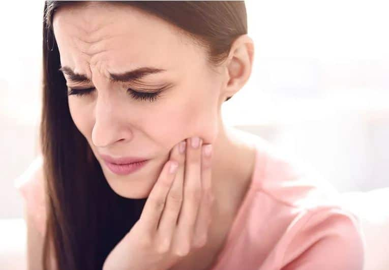 woman rubbing her jaw due to pain