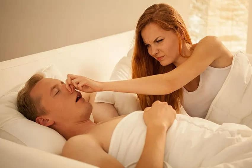 Woman plugs her man partners nose in bed because of his snoring