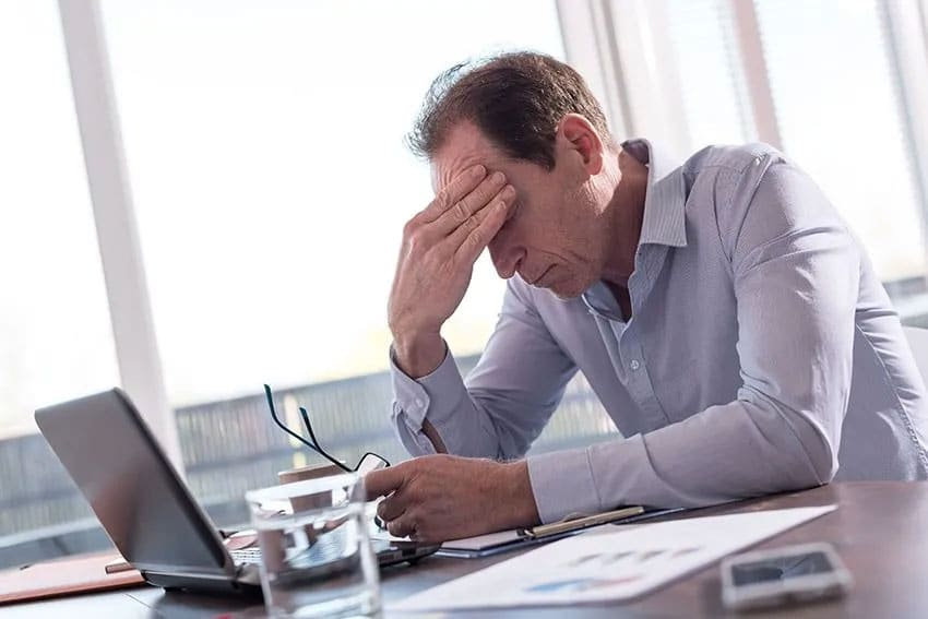 stressed out man sits at this computer with his hand resting on his head
