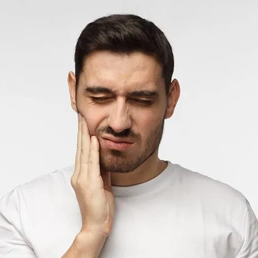 man with short black beard rubs the side of his mouth