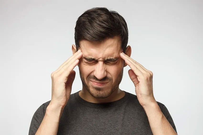 man placing pressure on the temples due to head pain