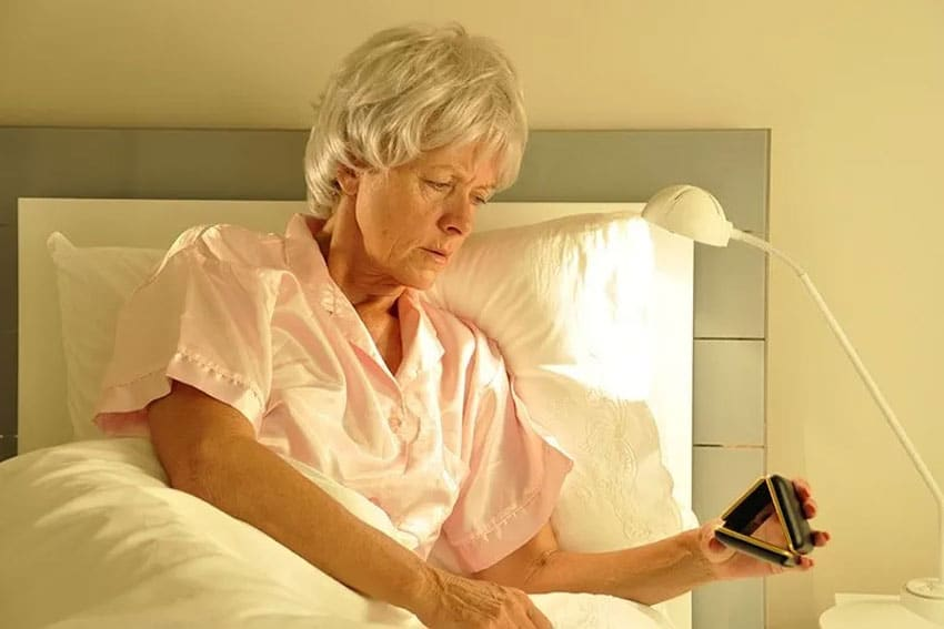 Older woman up at night looking at her alarm clock