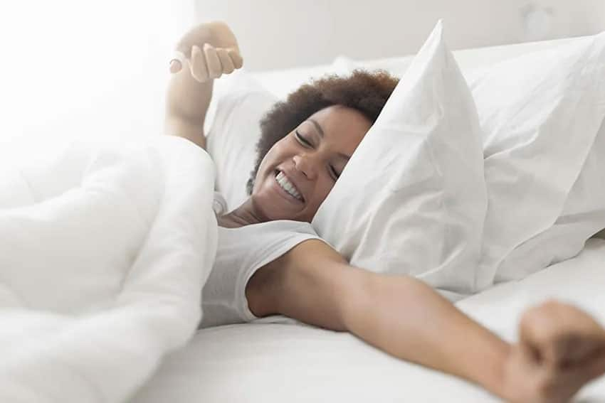 Woman waking up after a great nights sleep by stretching