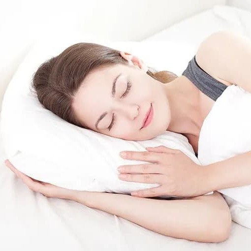 Woman peacefully sleeps on her side with her arm under her pillow