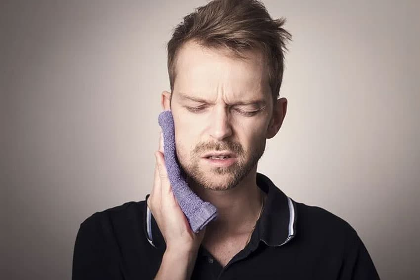 Man holds a warm warm cloth to his jaw, trying to reduce pain