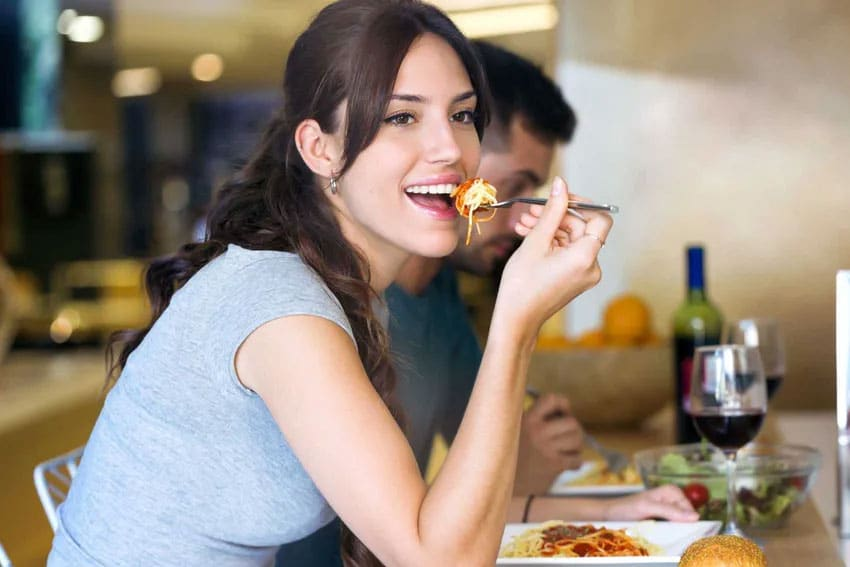 Beautiful woman eats a healthy, soft food diet at a counter at a restaurant