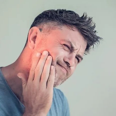 man rubs the side of his face due to jaw pain