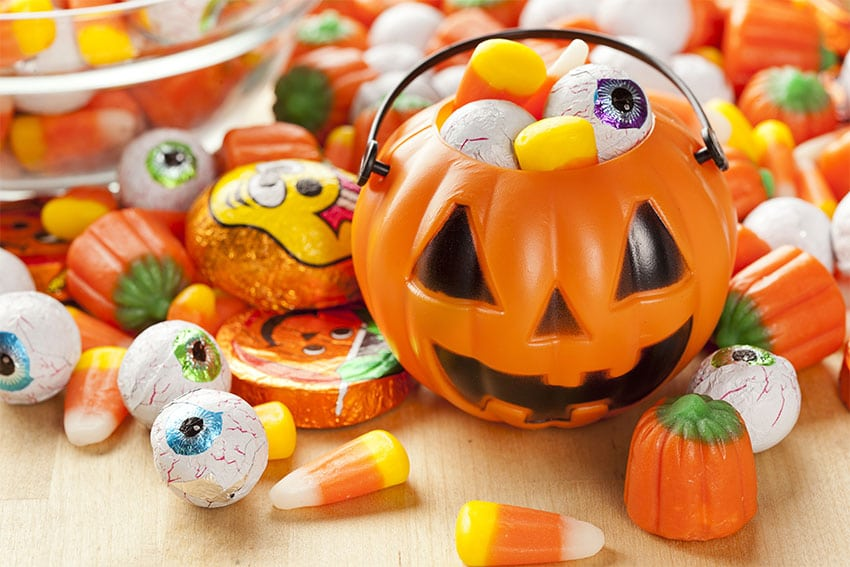 plastic pumpkin bucket overflowing with Halloween candy