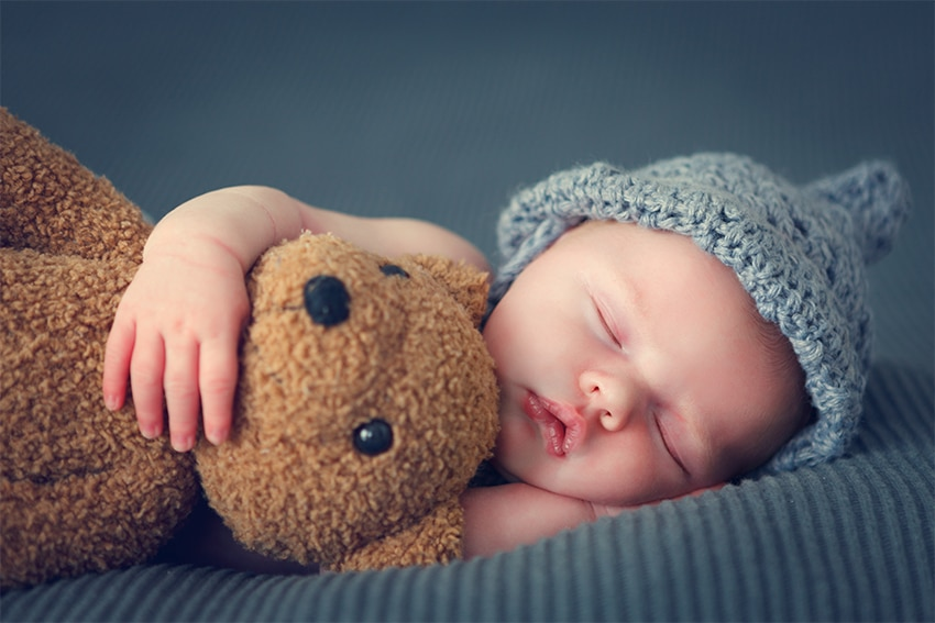little baby holding a teddy bear while sleeping
