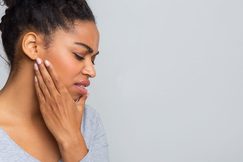 dark haired woman massaging her jaw due to pain