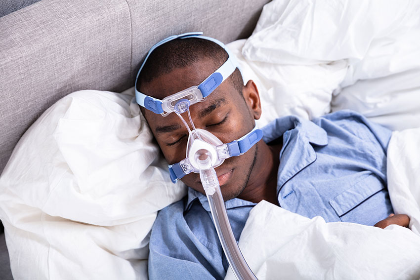 young man sleeping with CPAP mask on in bed