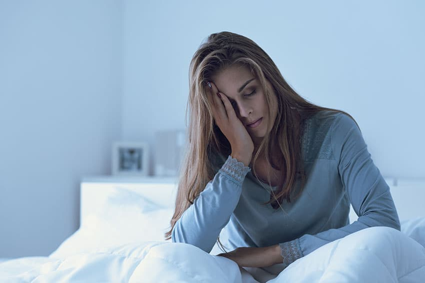 tired woman sitting on bed with a headache